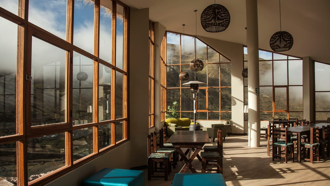 The common area at the Mountain Lodges of Peru in the Lares Region for trekkers, with tables, chairs, and well-positioned windows to maximize the view.