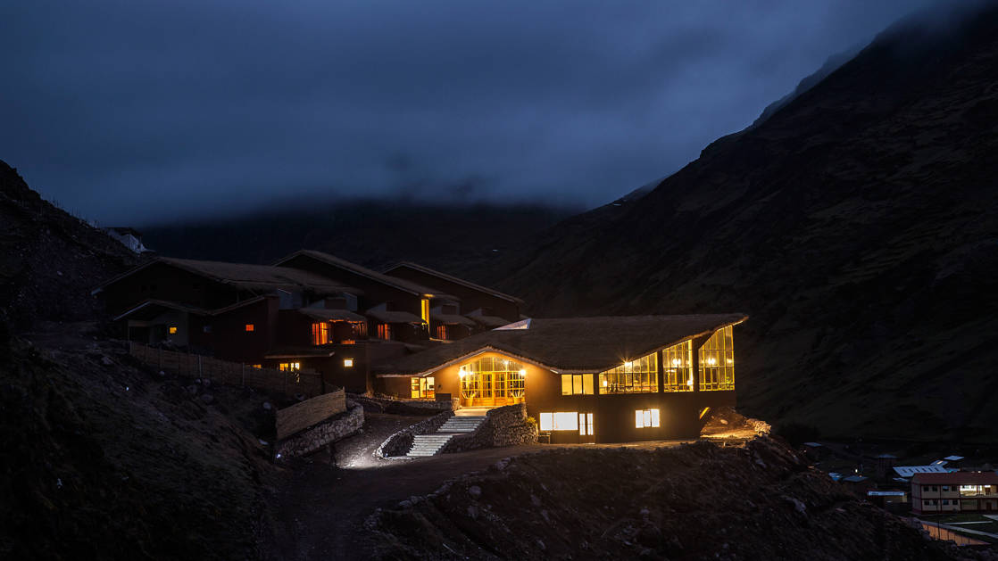 At night, lights glow from the windows of the mountain lodges in Peru's Lares region, a sustainable accommodation for trekkers