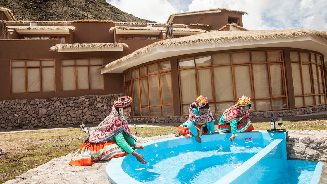 Women dressed in traditional Andean Highlands wear dip their hands in clear water from a fountain outside of the mountain lodges, a sustainable accommodation for trekkers in Peru's Lares region