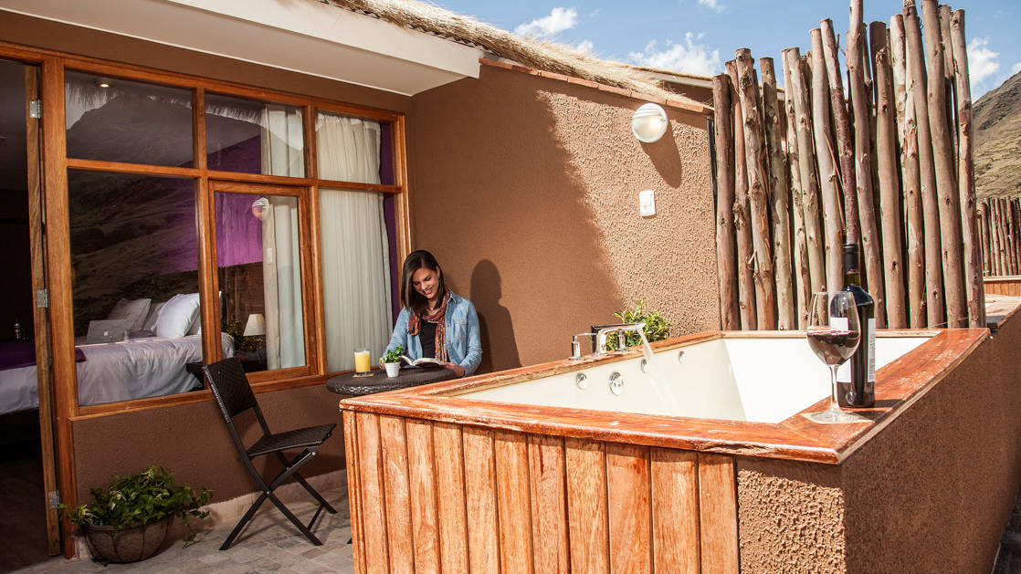 A woman reads on a table in the courtyard next to the hot tub at the mountain lodges in Peru's lares region, a sustainable accommodation for trekkers