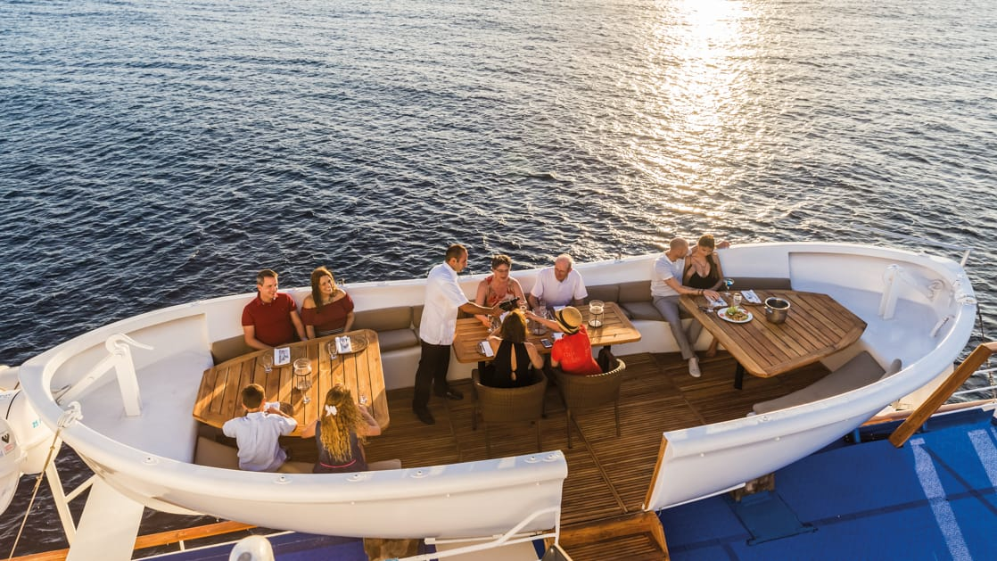 A group of guests dining in a converted lifeboat with booth seating on the Galapagos Legend deck.