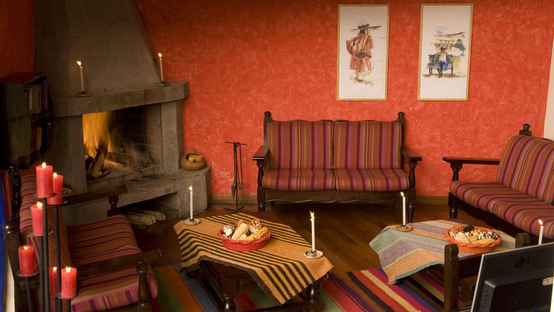 The lobby at Casa Andina Classic Cusco San Blas, in Cusco, Peru, is warm and inviting with a wood-fired stove, wooden benches, painted walls, artwork, and woven textiles.