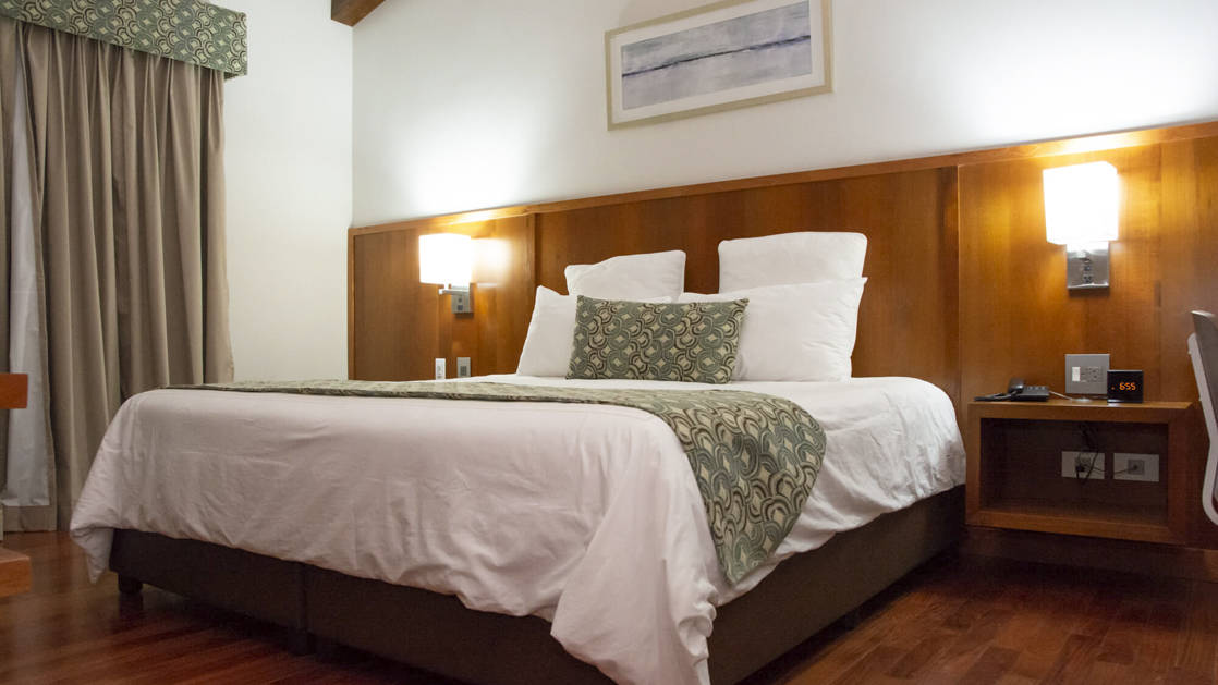 A guest room with a king-sized bed and reading lights at the family-owned Los Brezos Hotel, near the Baru Volcano in Panama
