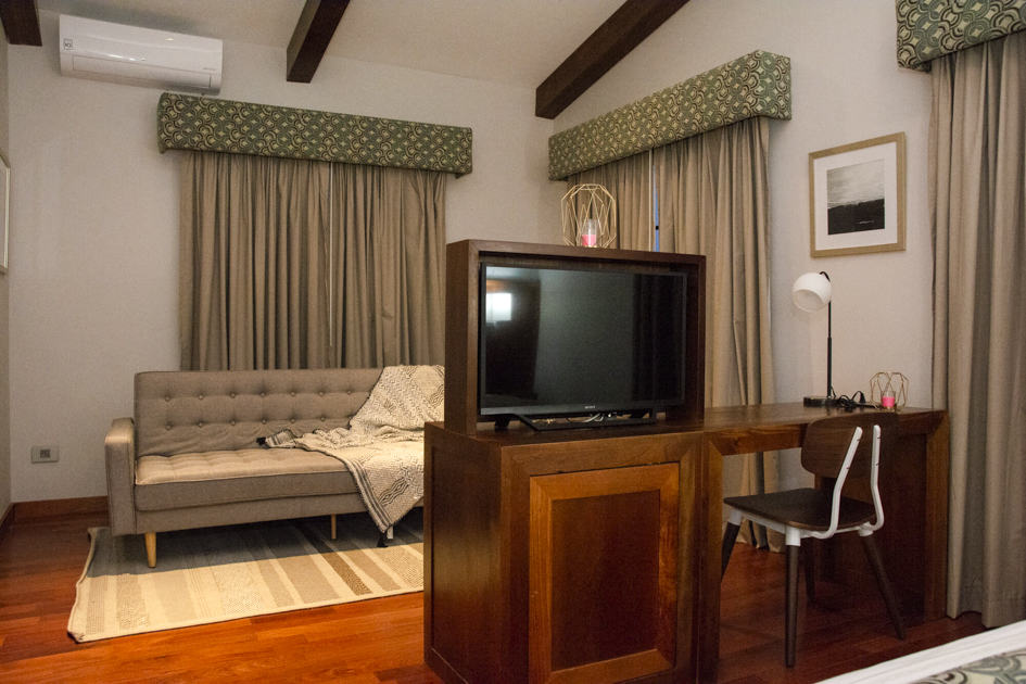 A guest room with a television, couch, king-sized bed and drapes at the family-owned Los Brezos Hotel, near the Baru Volcano in Panama