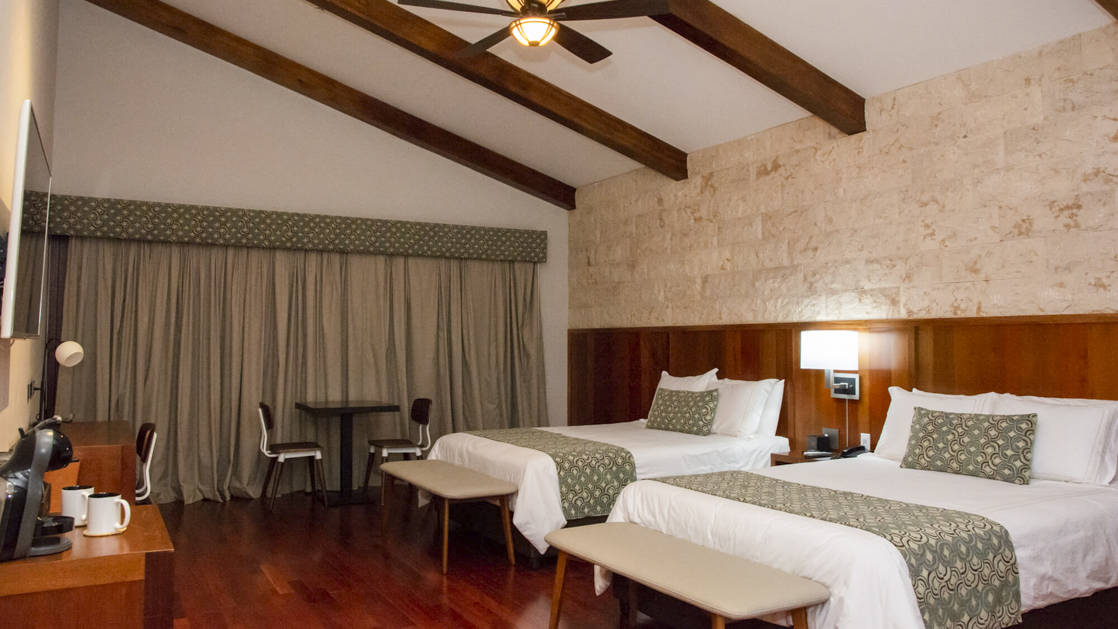 A guest room with two twin beds, wooden beams, a ceiling fan, drapes, and a television at the family-owned Los Brezos Hotel, near the Baru Volcano in Panama