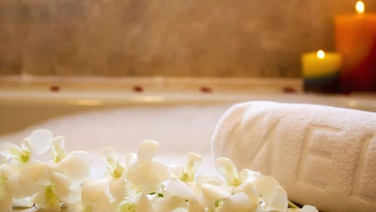 up close view of orchids and a branded towel in front of the bathtub at melia hotel panama canal