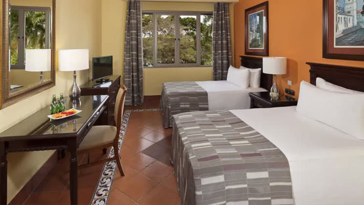 room with two crisp grey and white beds, table and chair and large window at melia hotel panama canal