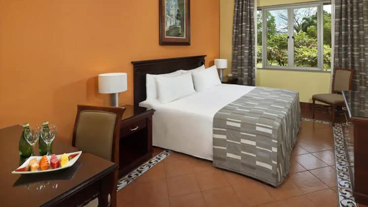 room with a large white bed with grey checked blanked on it, yellow wall and window at melia hotel panama canal