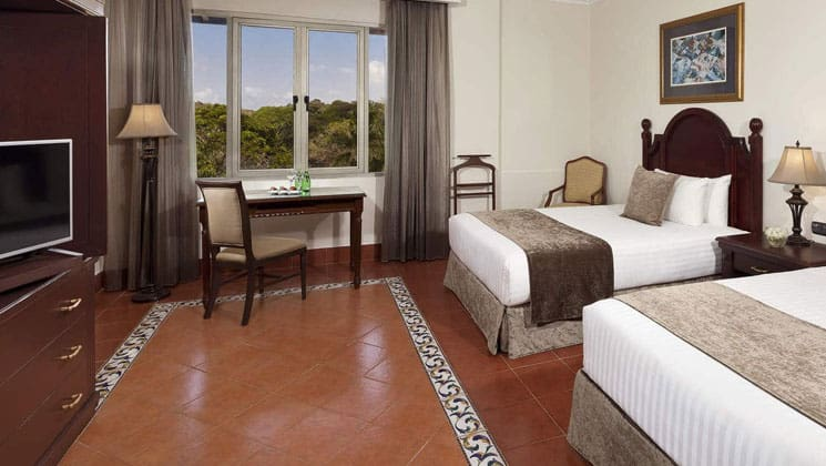 double room with table and chairs, orange floor and large picture window at melia hotel panama canal