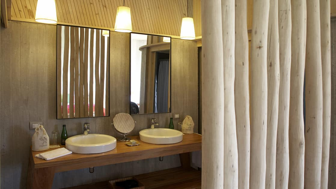 Two sinks and a mirror on the vanity inside a bathroom at Posada de Mike Rapu, a luxury eco hotel in a LEED-certified building.