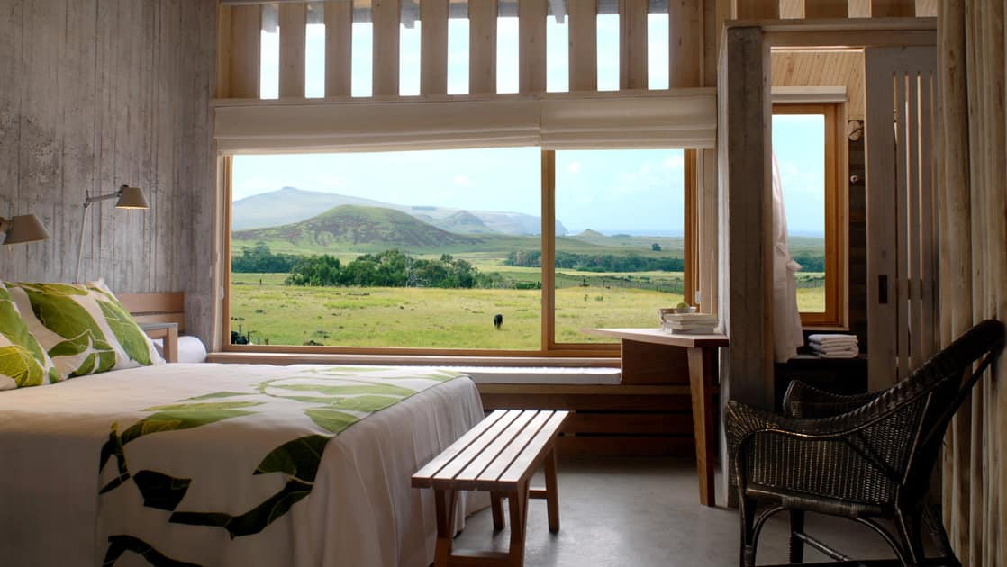 A room with a large window overlooking the mountains and green fields on Easter Island, with a full bed and modern furniture, at Posada de Mike Rapu, a luxury eco hotel.