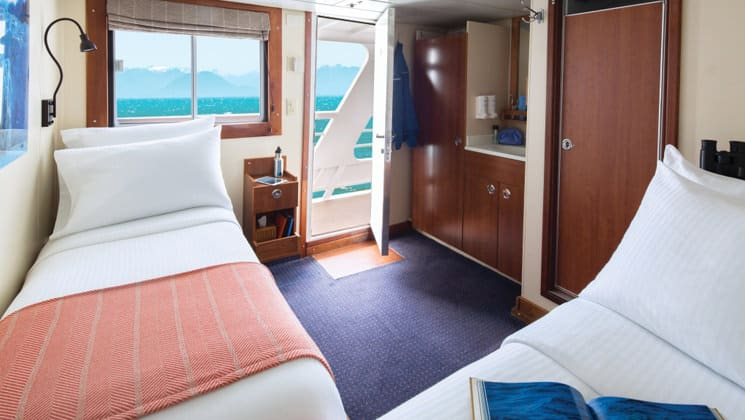 National Geographic Sea Lion Category 2 stateroom with 2 twin beds, closet, bathroom, picture window, and door that opens to deck.