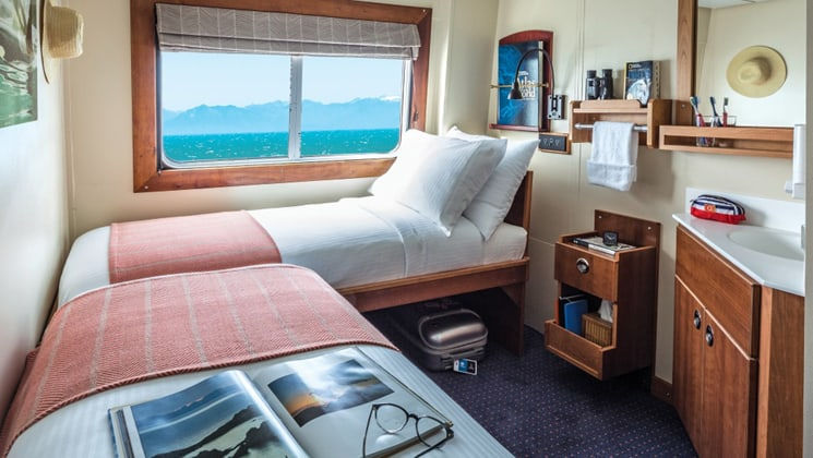 Category 1 Cabin 305 aboard National Geographic Sea Bird small ship, with 2 twin beds, picture window and small sink.
