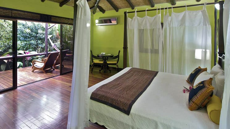 The deluxe room with a queen-sized bed, yellow walls, white linens, and a private patio at the Nayara Hotel, Spa & Gardens, a luxury boutique hotel in Costa Rica