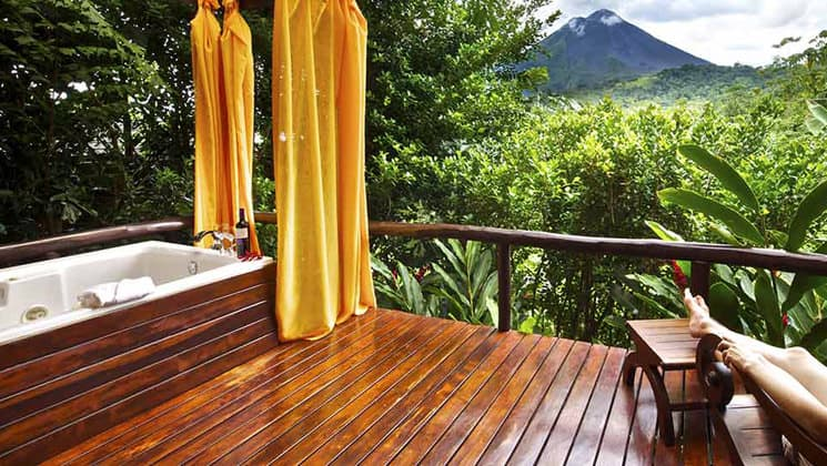 A person rests their legs on an ottoman on the deck, next to a jacuzzi, with a view of the Arenal Volcano National Park, adjacent to the Nayara Hotel, Spa & Gardens, a luxury boutique hotel in Costa Rica