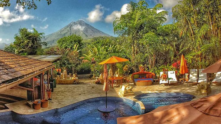 The pool, with umbrellas and lounge chairs, is set in a stone patio on the edge of the jungle with a view of the volcano at Nayara Hotel, Spa & Gardens, a luxury boutique hotel in Costa Rica