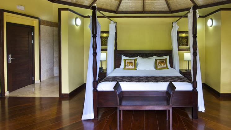 A room with a queen-sized bed, yellow walls, traditional woodwork, a mosquito net at the Nayara Hotel, Spa & Gardens, a luxury boutique hotel in Costa Rica