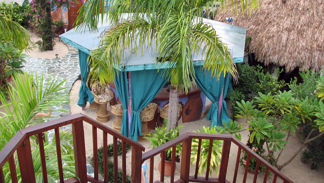 Overlooking the main bar surrounded by palm trees and thatched roof villas at Chabil Mar Villas in Belize