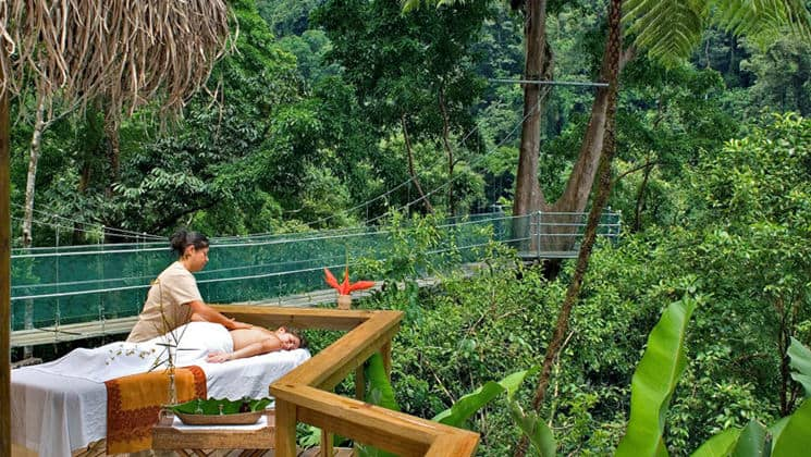 A guest receives a massage outdoors in a jungle setting at the Pacuare Lodge, a sustainable hotel in Costa Rica