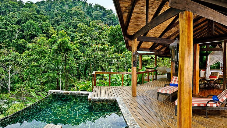 The pool at Pacure Lodge is set between an outdoor deck and the lush jungle, offering a relaxing wilderness ambience in Costa Rica