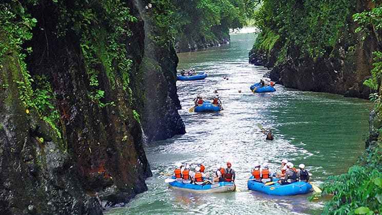 Rafters float down Costa Rica's Pacuare River between steep cliffs and lush vegetation.