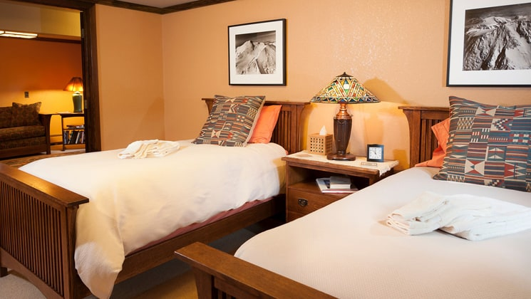 A room with two full beds, a nightstand, and reading lamp with artwork at the Parkside Guest House, a bed and breakfast in Anchorage Alaska