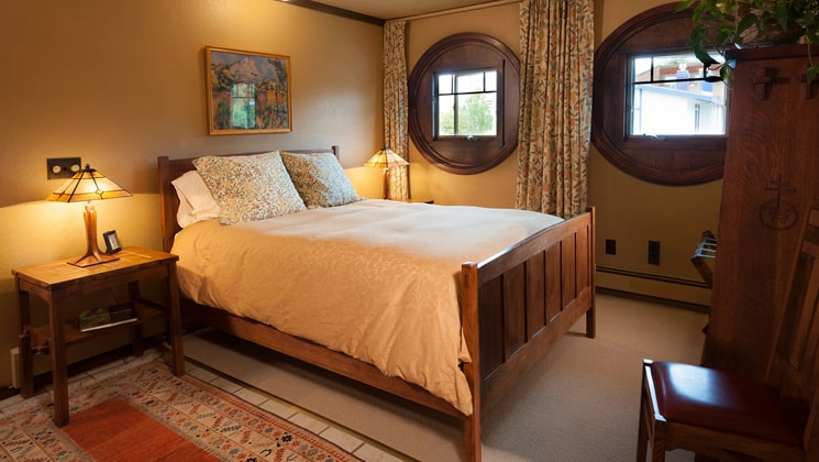 A room with one full bed, two windows, a reading lamp, and nightstand at the Parkside Guest House, a bed and breakfast in Anchorage Alaska