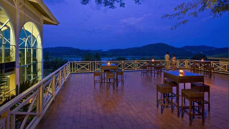 Two people stand on the patio at night, with candlelit tables and unobstructed views at Gamboa Rainforest Resort in Panama