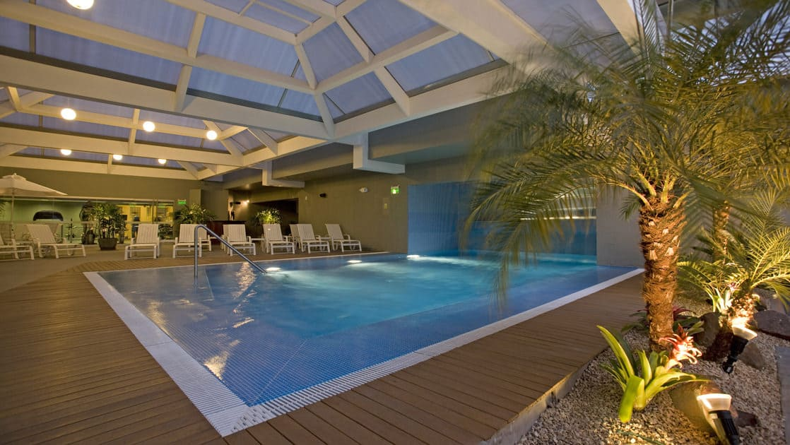 The indoor pool at Casa Andina Private Collection Miraflores, with lounge chairs and a palm tree, is a respite for guests traveling in Peru.