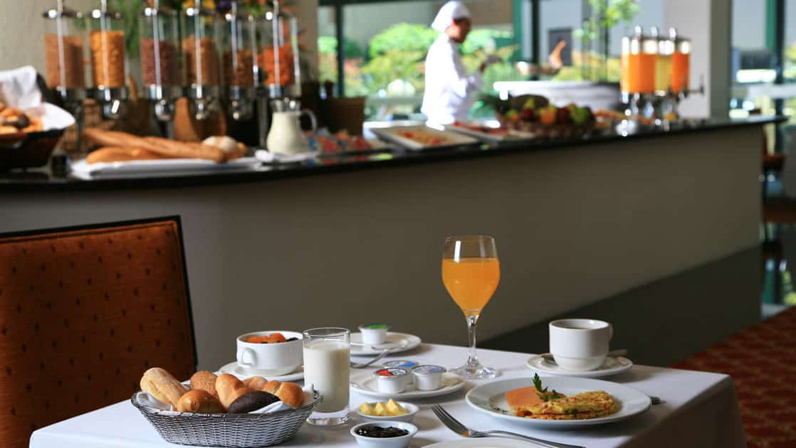A table is set with fresh orange juice, an omelet, and a basket of bread during the breakfast buffet at Casa Andina Private Collection Miraflores, serving regional ingredients in Peru.