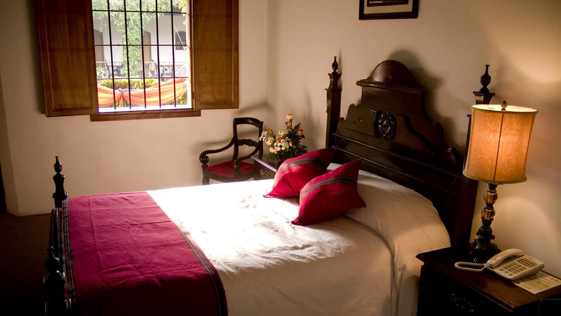 A room with a double bed, decorated in the colonial style of Antigua, inside the historic, renovated Hotel Posada Don Rodrigo