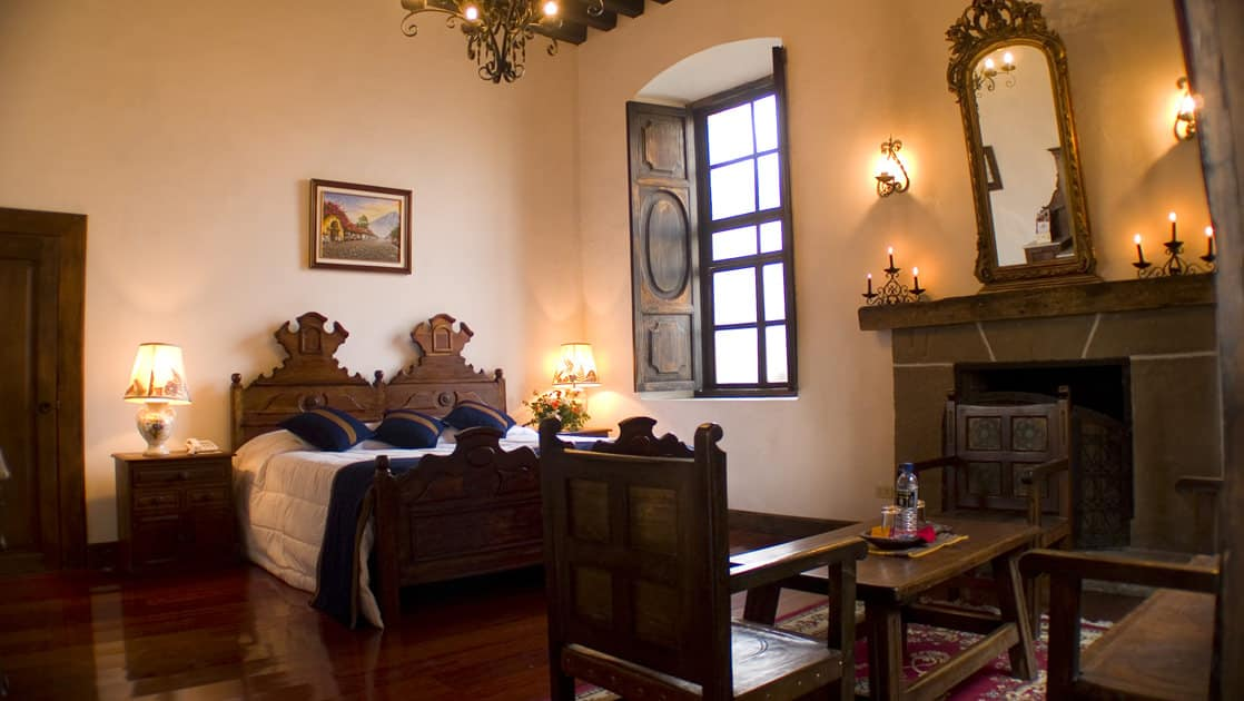 A room with a full bed, decorated in the colonial style of Antigua, inside the historic, renovated Hotel Posada Don Rodrigo