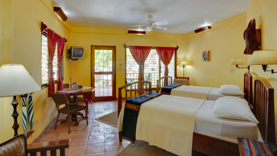 A room with yellow walls, window views, and two double beds at the Inn at Robert's Grove, a boutique hotel ideal after a day exploring Belize's barrier reef or tropical rainforest