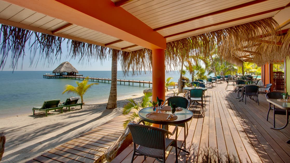 Tables are set for a relaxing oceanfront meal on the deck, next to the beach, at the Inn at Robert's Grove, a boutique hotel ideal after a day exploring Belize's barrier reef or tropical rainforest