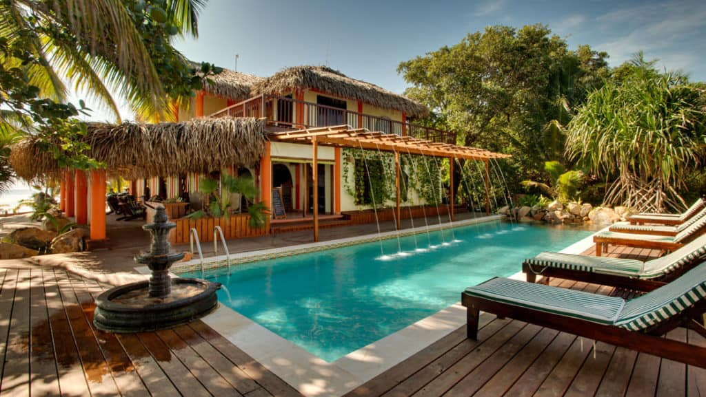 The pool with lounge chairs and umbrellas at the Inn at Robert's Grove, a boutique hotel ideal after a day exploring Belize's barrier reef or tropical rainforest