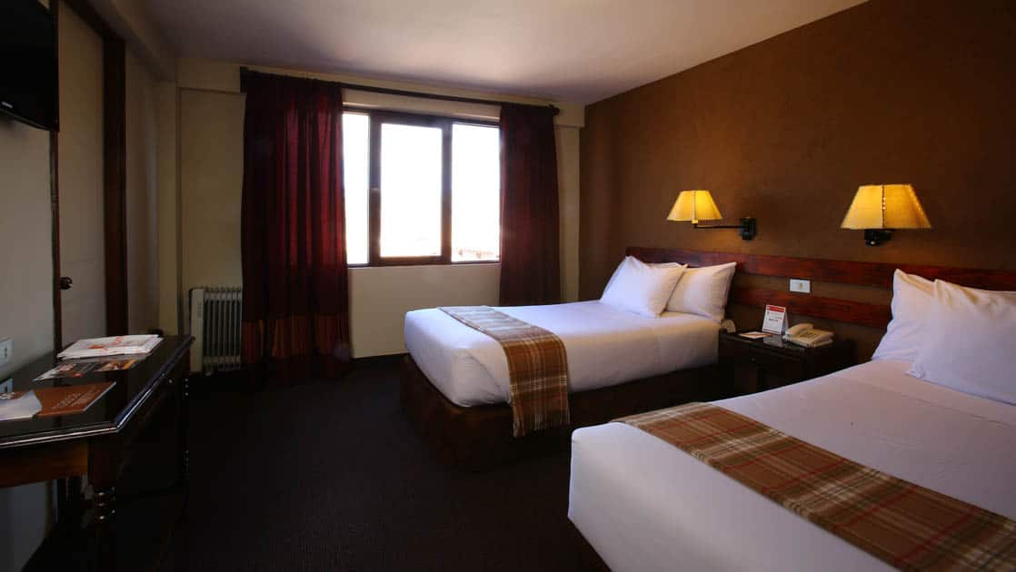 A room with two queen-sized beds, fresh linens, lamps, and a large window at the Casa Andina Classic Cusco San Blas, a quiet and cozy hotel in Cusco, Peru