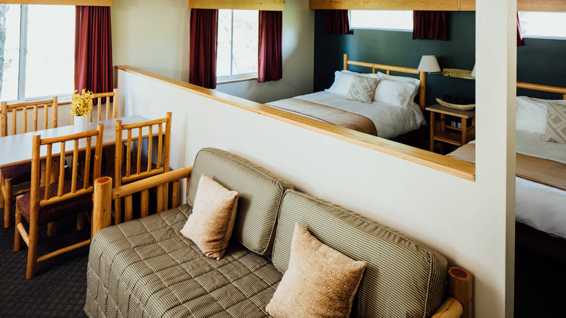 A couch, a table with chairs, and a mirror reflecting the bed inside the suite at the Seward Windsong Lodge, a stopover for exploring the Kenai Fjords National Park in Alaska