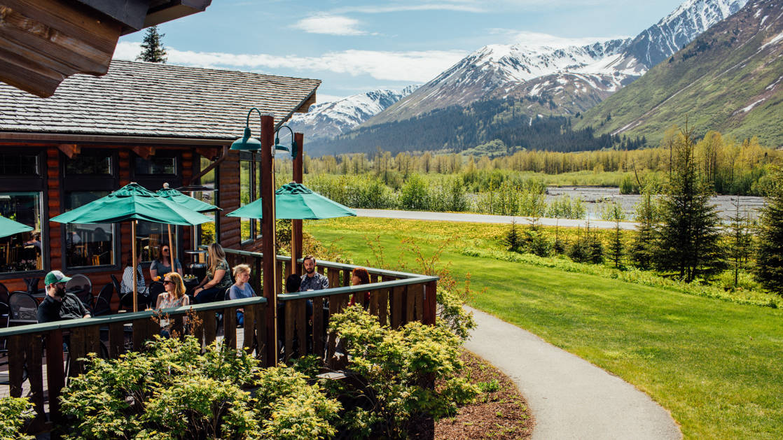 Green umbrellas are opened on the deck outside of the Seward Windsong Lodge, while a path winds around the building through gardens and toward Alaska's snow-capped mountains