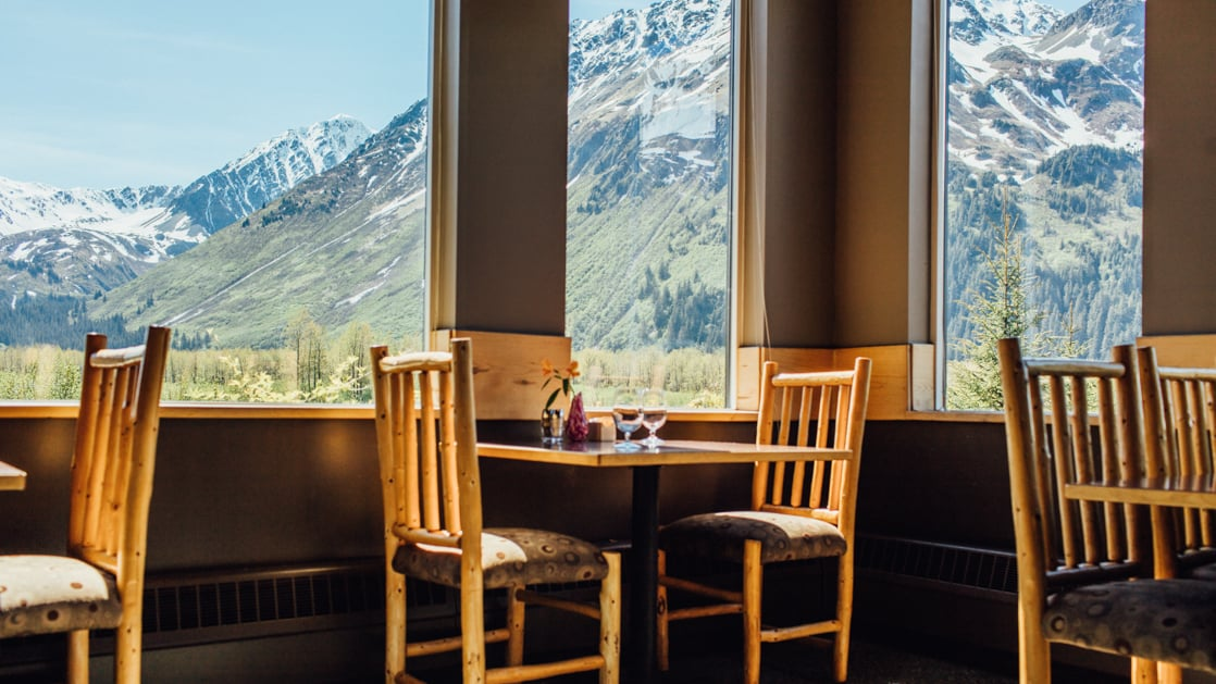 Tables and chairs next to large windows facing a view of the snow-capped mountains at Seward Windsong's gourmet restaurant, Resurrection Roadhouse, in Alaska