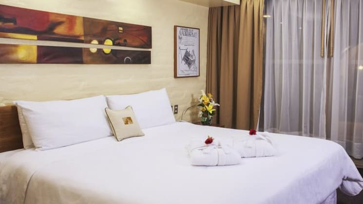 A room with a king-sized bed, white sheets, artwork, and drapes at Sonesta Posada Del Inca Arequipa, a luxury boutique hotel