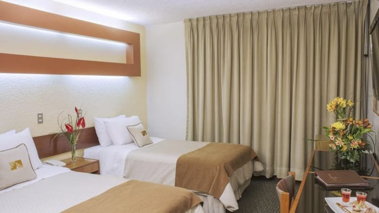 A room with two twin beds, artwork, and drapes at Sonesta Posada Del Inca Arequipa, a luxury boutique hotel