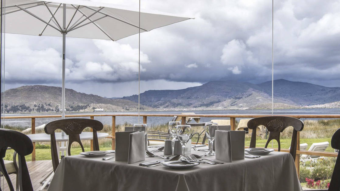 Tables are set on a balcony wiith a view of Lake Titicaca, for guests to dine at Sonesta Posadas del Inca, a lodge in the Andes