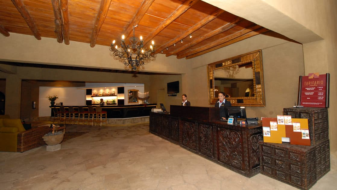 The front desk with wood ceilings, a chandelier, and traditional design at Sonesta Posadas Del Inca in Peru's Sacred Valley, a boutique hotel near Machu Picchu.