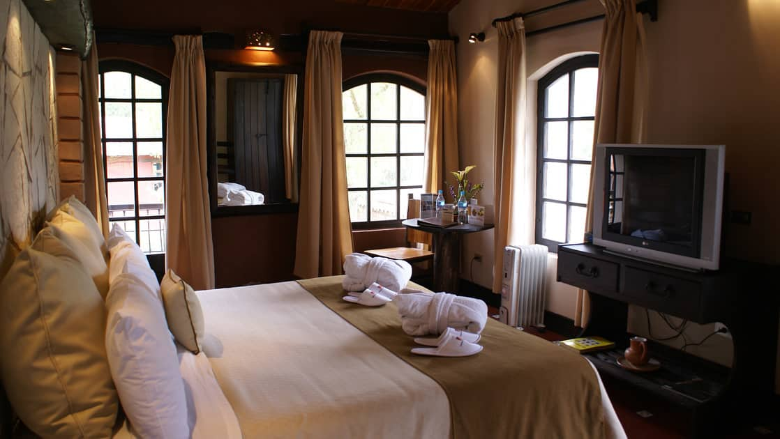 The standard room features a king-sized bed, television, and large windows at Sonesta Posadas Del Inca in Peru's Sacred Valley, a boutique hotel near Machu Picchu.