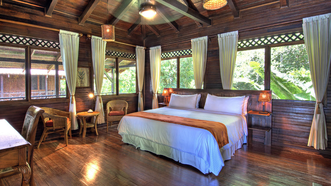 An upstairs balcony room with a king-sized bed, curtains, windows, tables, and chairs at the Tortuga Lodge, a luxury sustainable resort in Costa Rica.
