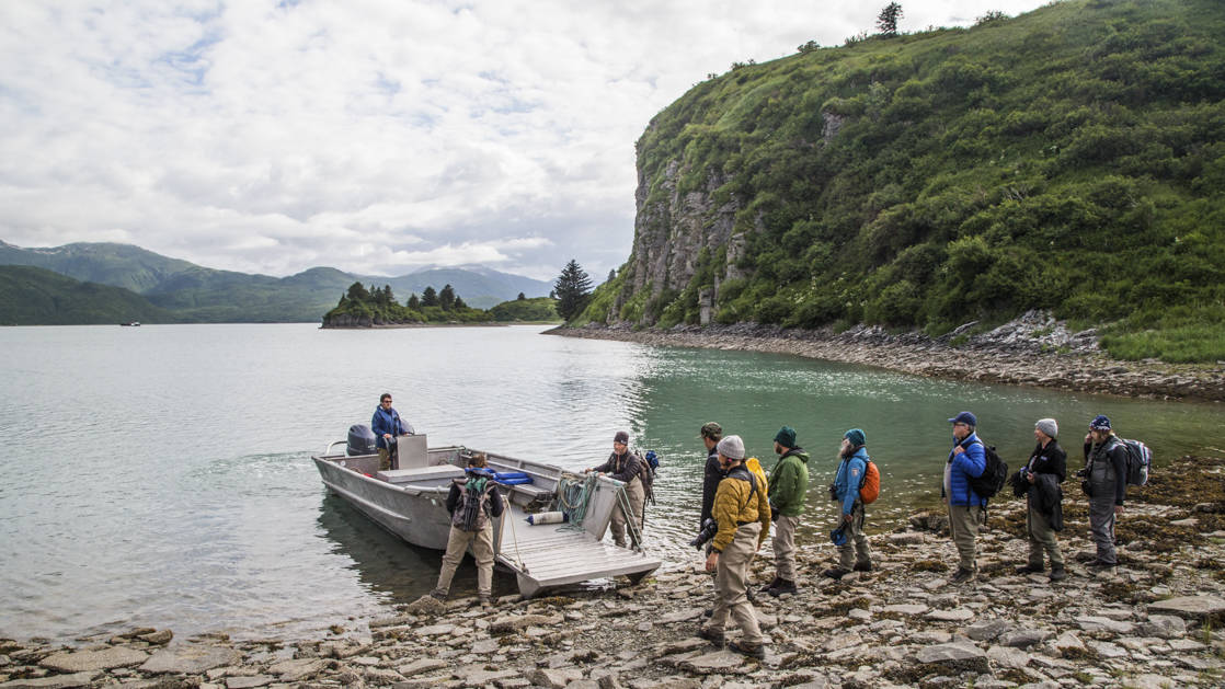 Guests getting off the skiff on shore in Alaska.