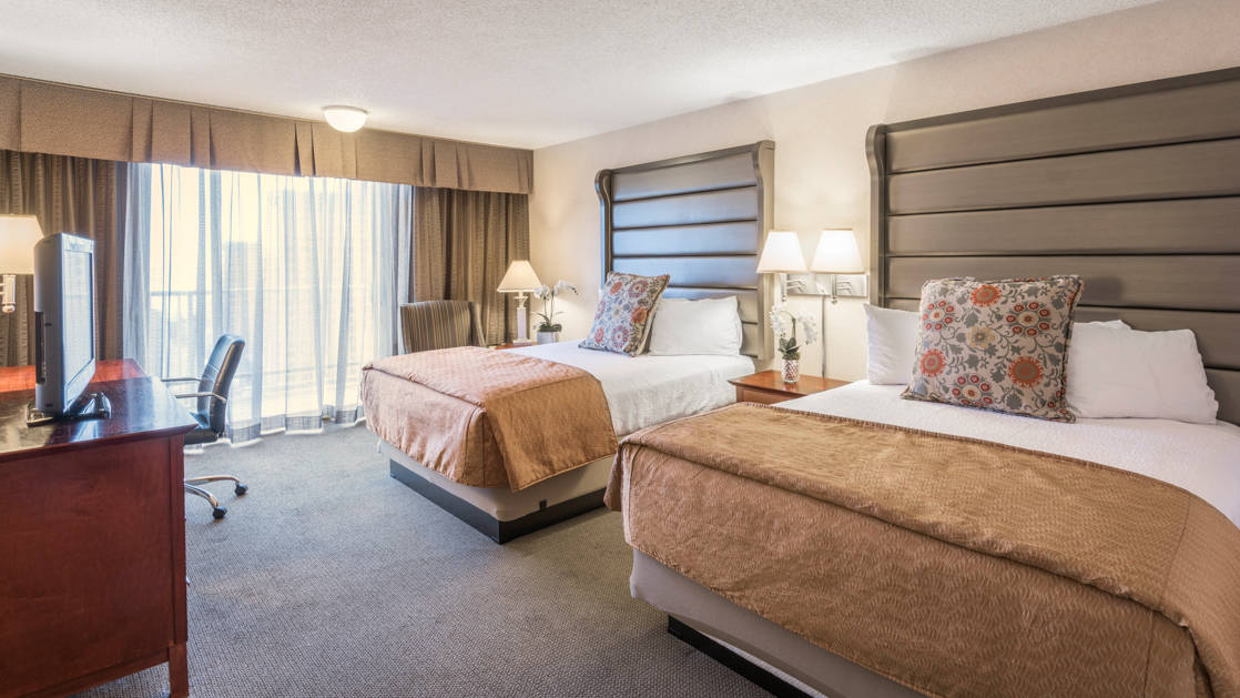A standard room with two queen-sized beds, a dresser, reading lamps, and nightstand at the Westmark Anchorage, a downtown hotel that was recently renovated