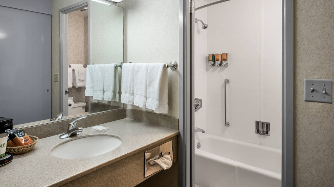 A bathroom inside a guest room with sink, vanity, and hot shower at the Westmark Anchorage, a downtown hotel that was recently renovated