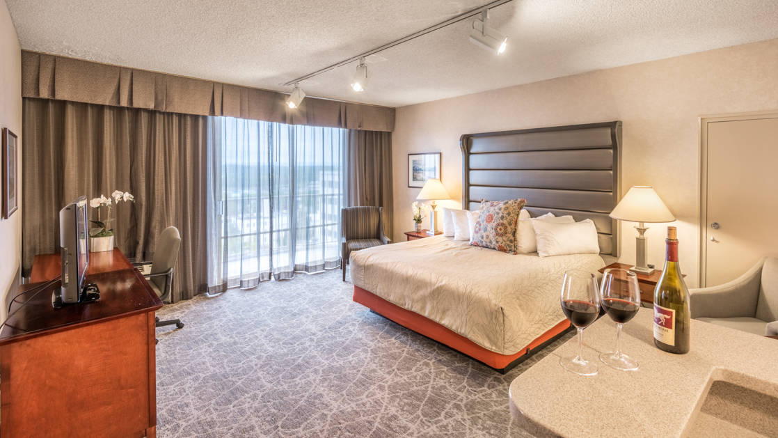 A suite with a king-sized bed, private terrace, and two glasses of red wine at the Westmark Anchorage, a downtown hotel that was recently renovated