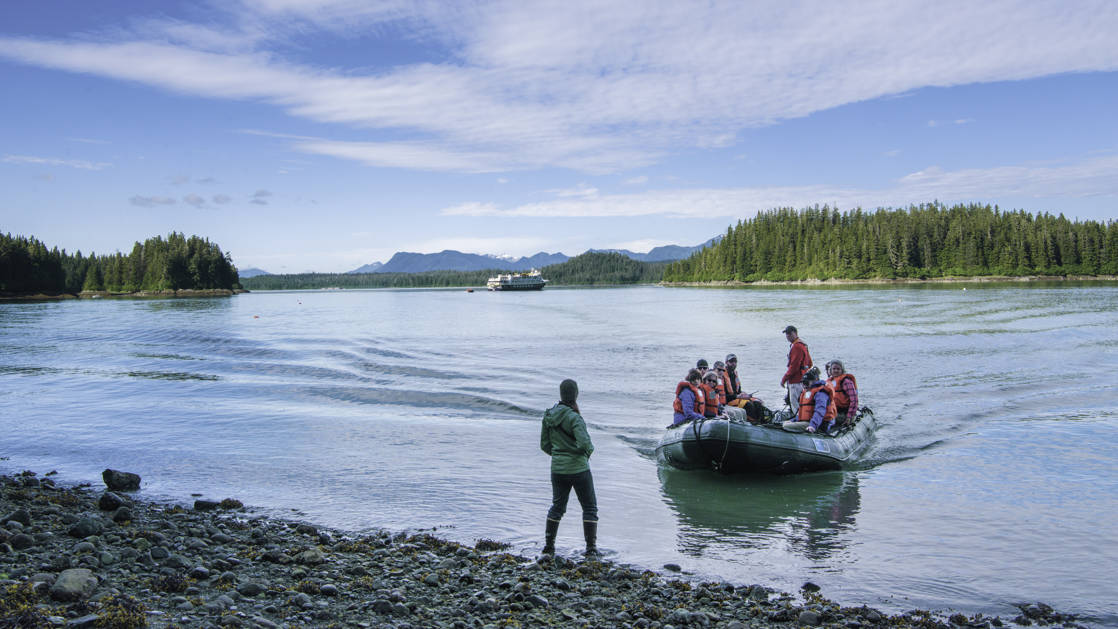 adventure travelers hiking in Cascade Creek Trail, Thomas Bay, Tongass National Forest, Southeast Alaska, with a skiff waiting to pick them up